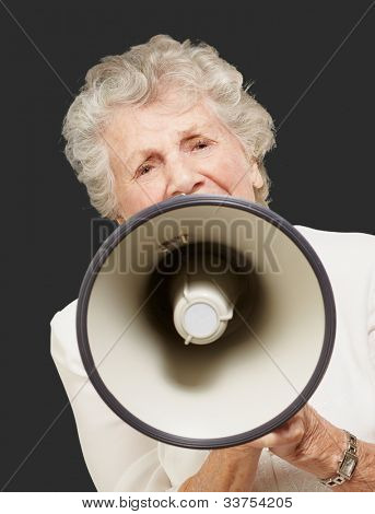 portrait of a senior woman screaming with a megaphone over a black background
