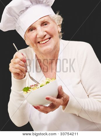 portrait of an adorable senior woman cook eating a salad against a black background