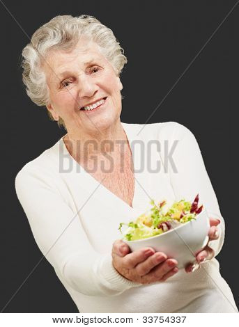 portrait of a senior woman showing a fresh salad over a black background