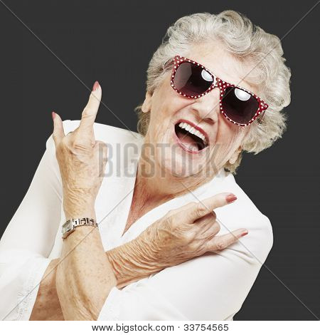 portrait of a senior woman doing a rock symbol over a black background