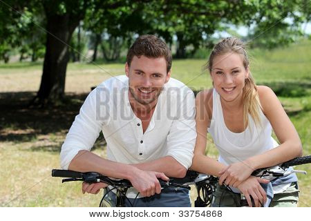 Portrait of cheerful couple riding bicycle in countryside