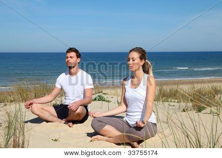 Couple doing yoga exercices on a sandy beach