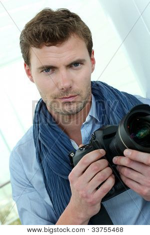 Handsome guy holding photo camera