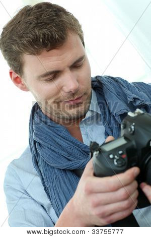 Handsome guy holding photo camera