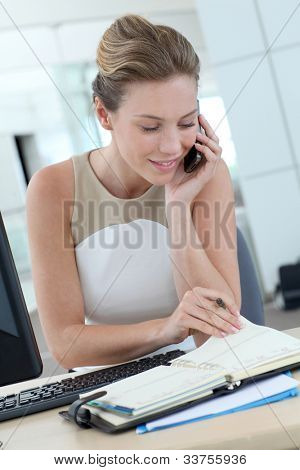 Businesswoman at her desk booking meeting hours on agenda