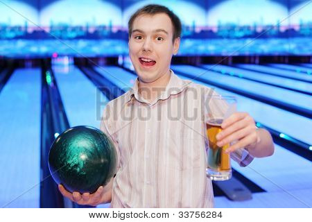 Happy young man shouts, holds green ball and glass of beer in bowling club
