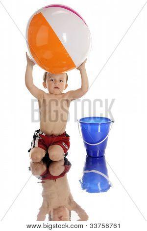 Uma adorável preschooler pegando uma bola de praia à beira da água.  Sobre um fundo branco.
