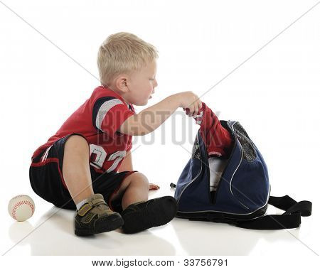 An adorable young preschooler pulling items from his sports bag, a baseball at his side.  On a white background.