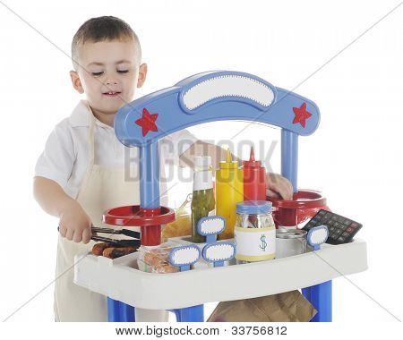 Un joven niño preescolar felizmente asar salchichas en su stand de venta.  Signos del stand quedan blan