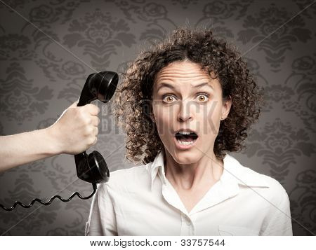 woman attending a phone call with surprise