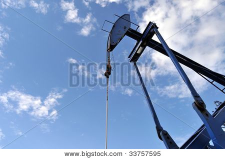 Closeup de ángulo bajo un conector azul de la bomba contra el cielo en un pozo de petróleo