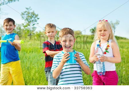 Kids group with toy water guns and other water containers