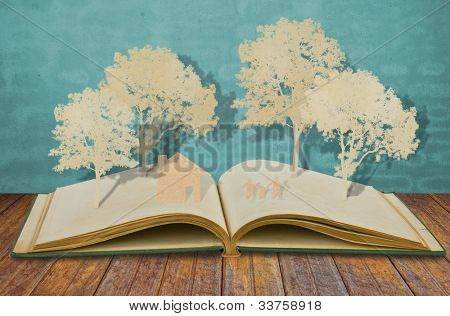 Paper cut of family symbol on old book  ( House,Tree,Mom,Dad,Child  )