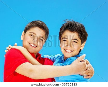 Cute boys smiling over blue sky, preteens playing outdoor, kids holding hands, best friends hug, beautiful children having fun, happy brothers, family joy and happiness concept