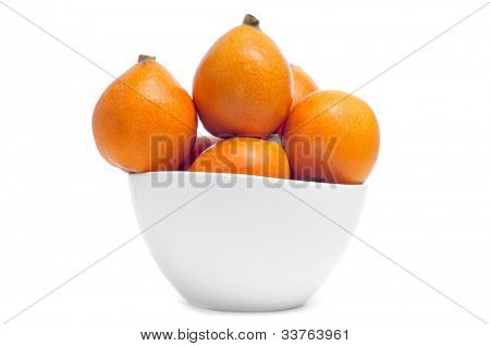 a bowl with loquats on a white background