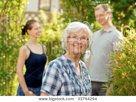 Senior woman smiling in front of two young people, outdoors
