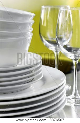 Plain White Plates Bowls With Crystal Wine Glasses On Stainless Steel Counter