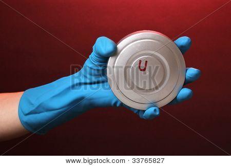 Uranium in hand on red background