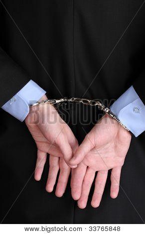 Mãos de empresário restringidas com algemas