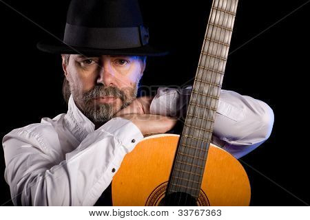 Portrait of popular musician with a guitar on black.