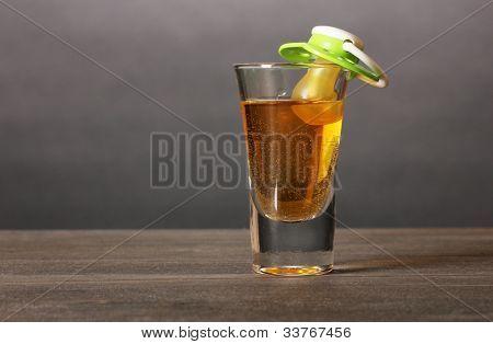 Baby dummy with alcoholic beverage on grey background