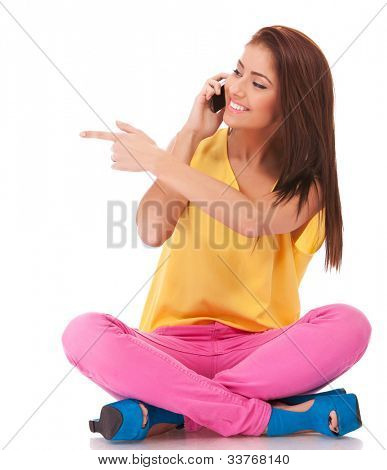 happy casual female talking on cell phone and gesturing with pointed finger to her right side