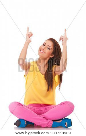 seated young casual woman pointing up over her head with both her hands on white background