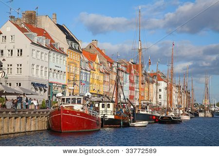 COPENHAGEN, DENMARK - AUGUST 25: unidentified people in open cafees of the Nyhavn promenade on August 25, 2010 in Copenhagen, Denmark. Nyhavn district is one of the most famous landmark of Copenhagen.