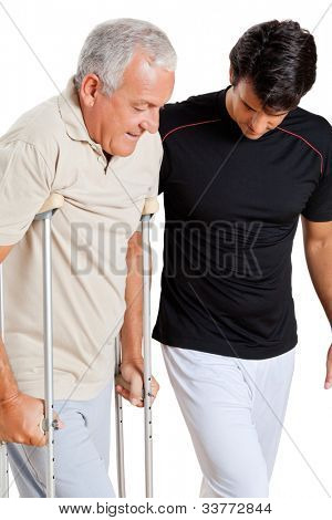 Trainer helping senior man with crutches to walk over white background