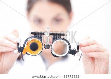 Optometrista manteniendo un ojo prueba gafas.
