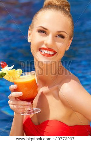 Beautiful woman smiling in enjoyment and pleasure sitting poolside with a glass of tropical cocktail