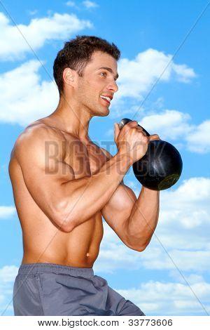 muscular Man mit Gewichten arbeiten im freien