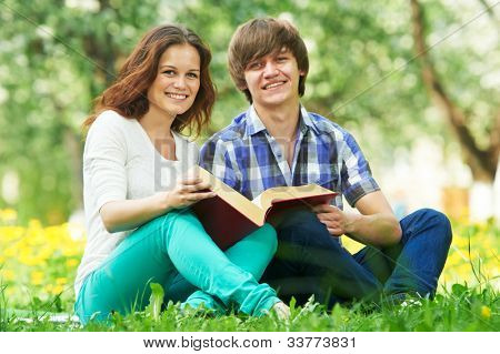 Group of two young students studying with book in spring outdoors park