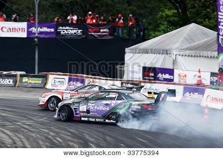 KUALA LUMPUR - MAY 19: Japan's Max Orido and Daigo Saito (back) drift in tandem at the Nations Cup competition during the Formula Drift 2012 Asia Round 1 on May 19, 2012 in Speedcity, Malaysia.