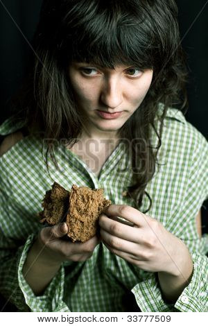 portrait of a poor beggar woman with a piece of bread in her hands