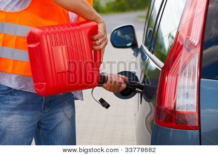 Man pouring fuel into the gas tank of his car from a red gas canister.