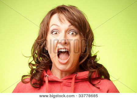 Screaming shocked woman over bright green background