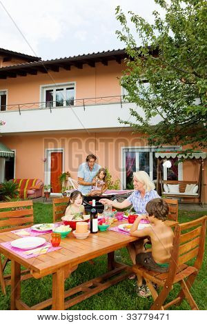 Family having a barbecue in the garden, eating