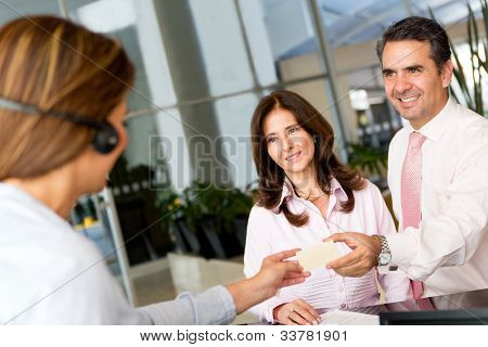 Business couple paying the hotel by credit card