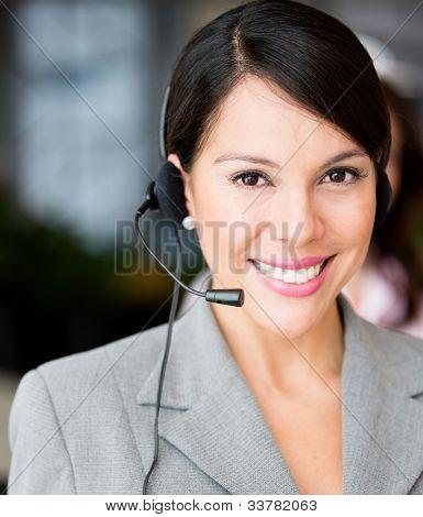 Recepcionista simpática sorridente e vestindo um fone de ouvido