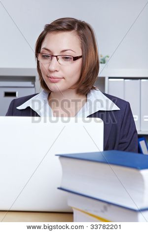 Attractive female laywer working at laptop computer in the office