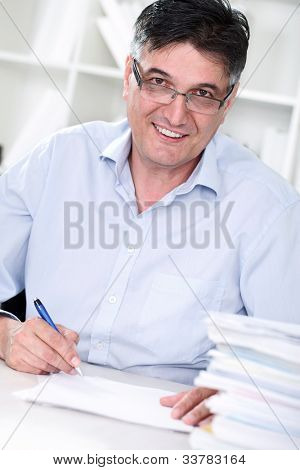 Smiling senior professor review tests in his office