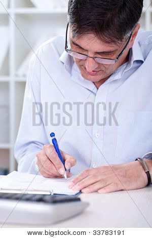 Business man sitting in office with laptop writing note