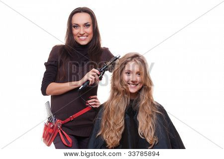 smiley hairdresser doing curly hair. isolated on white background