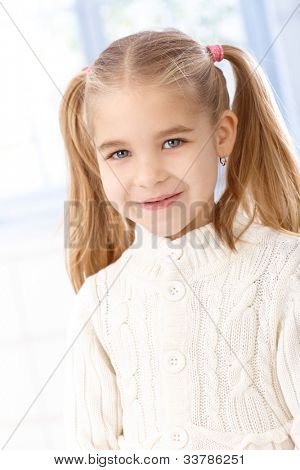 Portrait of cute little girl with ponytail, smiling, looking at camera.