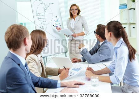 Team members listening attentively to a cheerful business woman holding a presentation