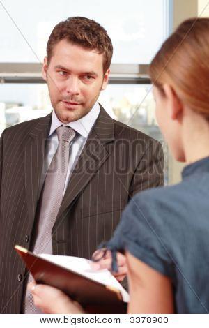 Chef im Gespräch mit seiner Sekretärin