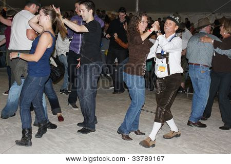TULSA, OK - OCT 20: Party goers dance and drink beer at Oktoberfest in TULSA, OK, on October 20, 2011 in TULSA, OK. Tulsa is the origin of the first Oktoberfest Chicken Dance in the United States.