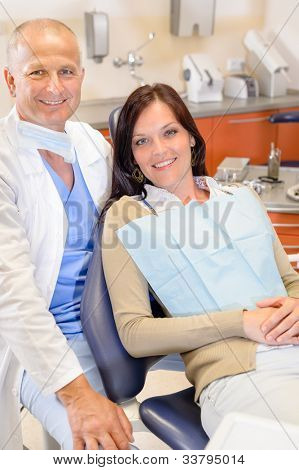 Woman at dental clinic surgery with male stomatology hygienist