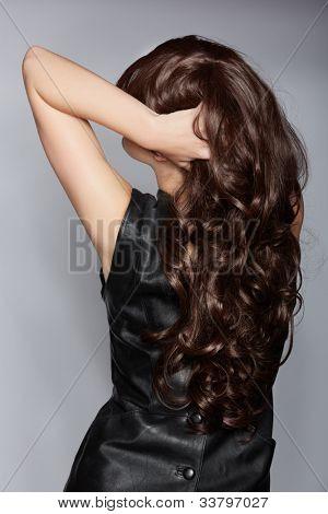 trás a mulher com cabelo encaracolado castanho longo, com brilho saudável, vestindo um couro vestido sobre uma viga